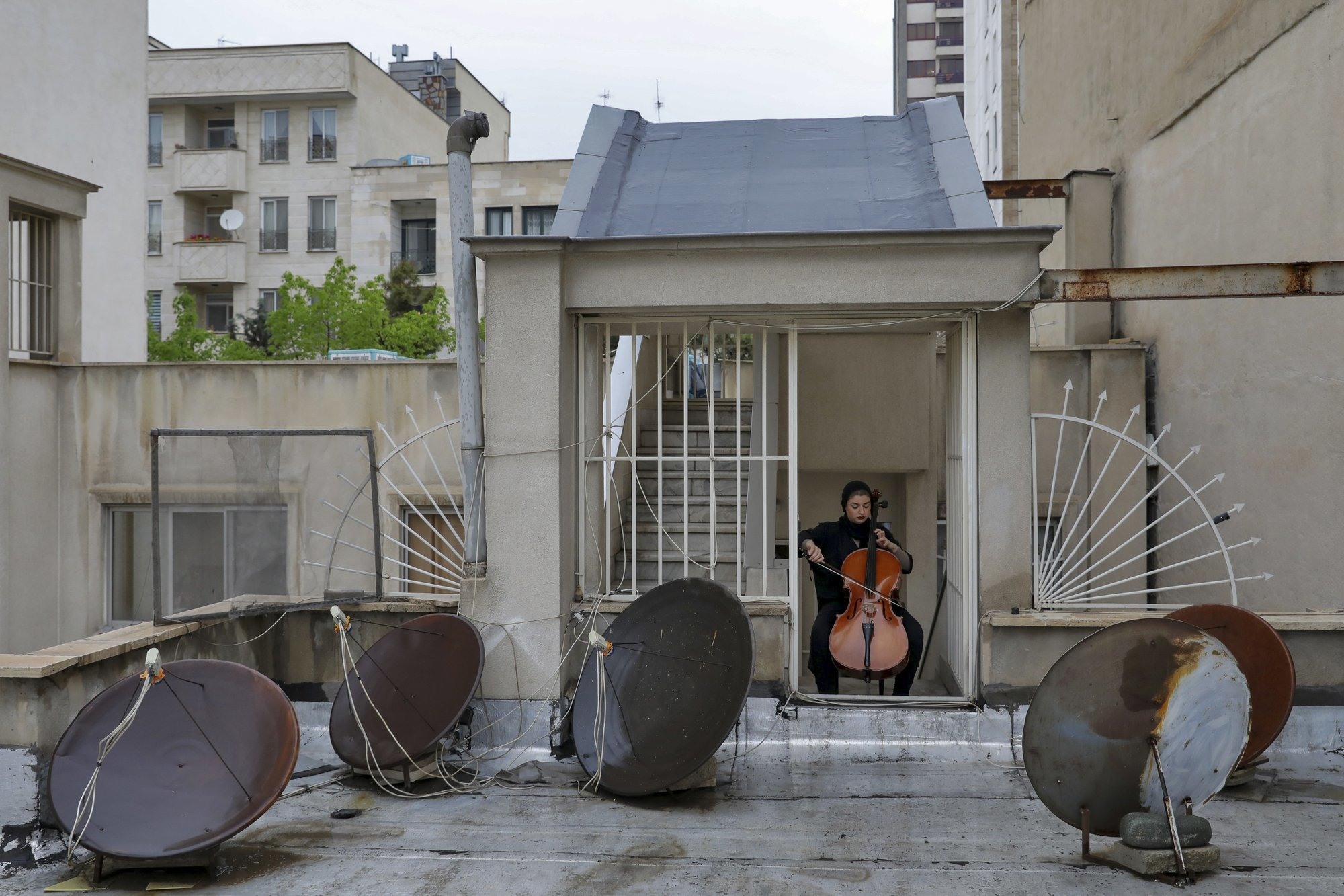 Yasamin Koozehgar, 22, plays cello on the roof of her home during mandatory self-isolation due to the new coronavirus disease outbreak, in Tehran Iran. (AP Photo/Ebrahim Noroozi)