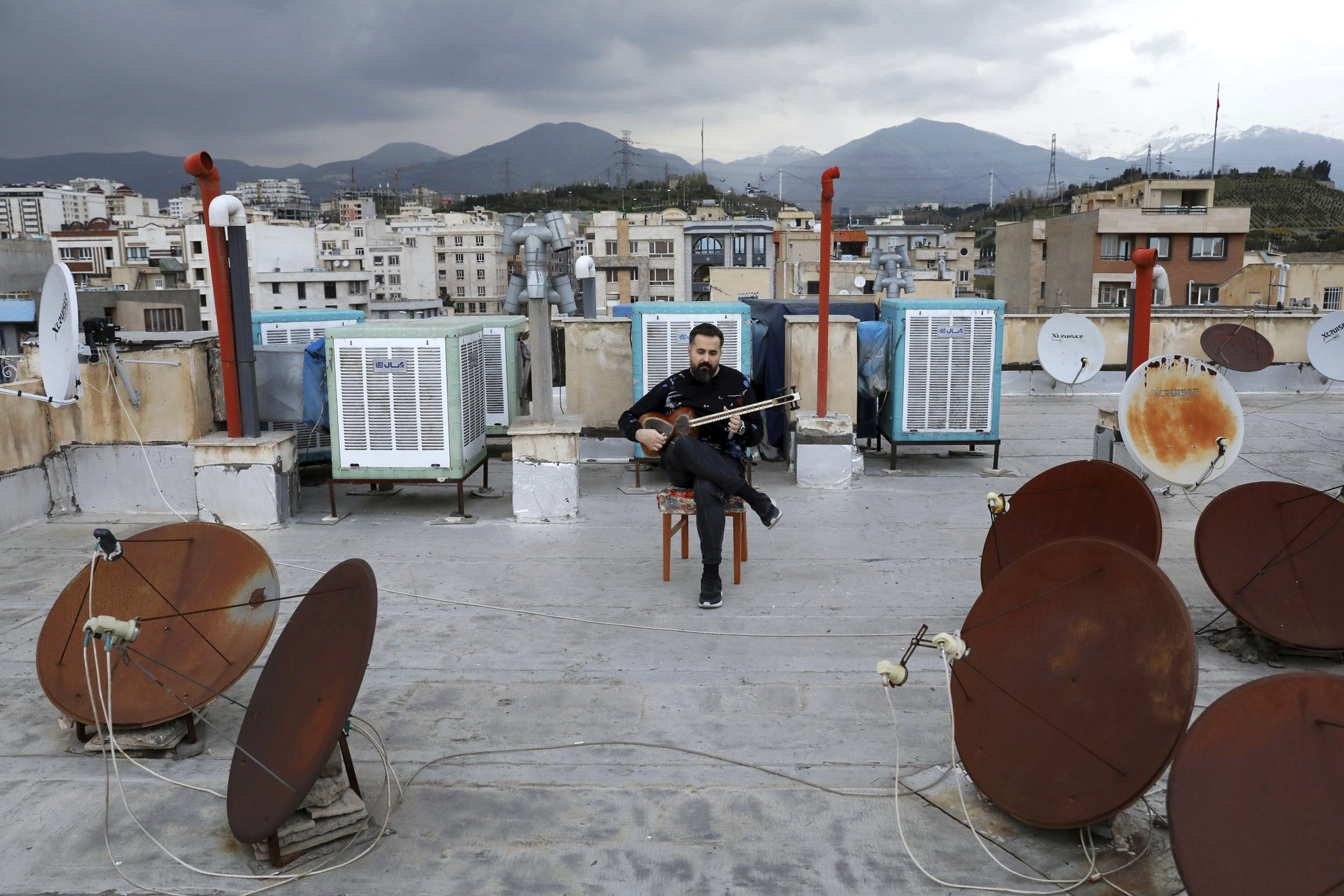 Composer and musician Midya Farajnejad, 36, plays tar on the roof of his home during mandatory self-isolation due to the new coronavirus disease outbreak, in Tehran Iran. (AP Photo/Ebrahim Noroozi)