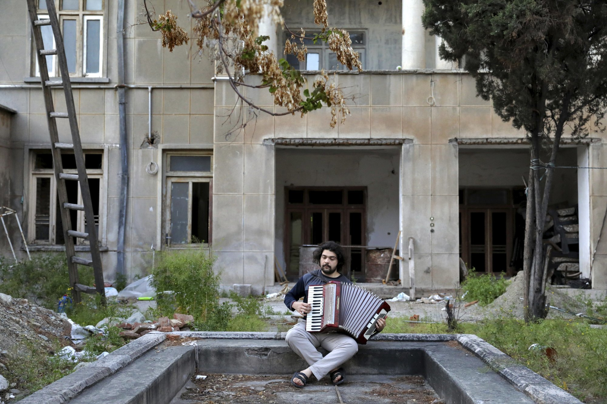 Kaveh Ghaffari, 26, plays accordion at the yard of his house during mandatory self-isolation due to the new coronavirus disease outbreak, in Tehran Iran. (AP Photo/Ebrahim Noroozi)