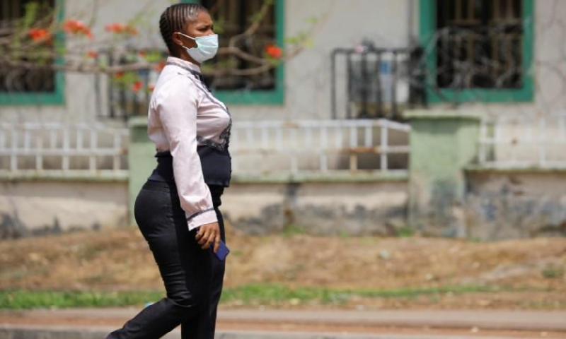 A woman wearing a protective face mask walks across the road, as the spread of Covid-19 continues in Abuja Nigeria, March 24. — Reuters