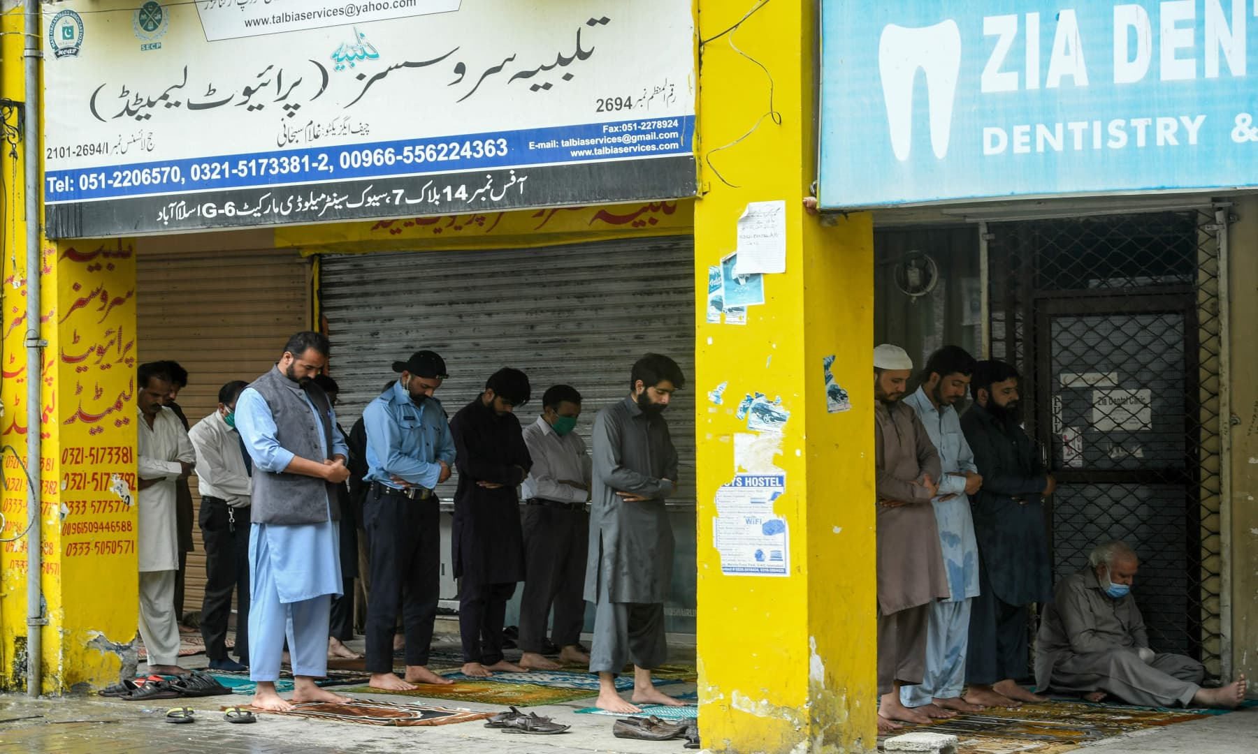 People offer Friday prayers outside a mosque in Islamabad. — AFP