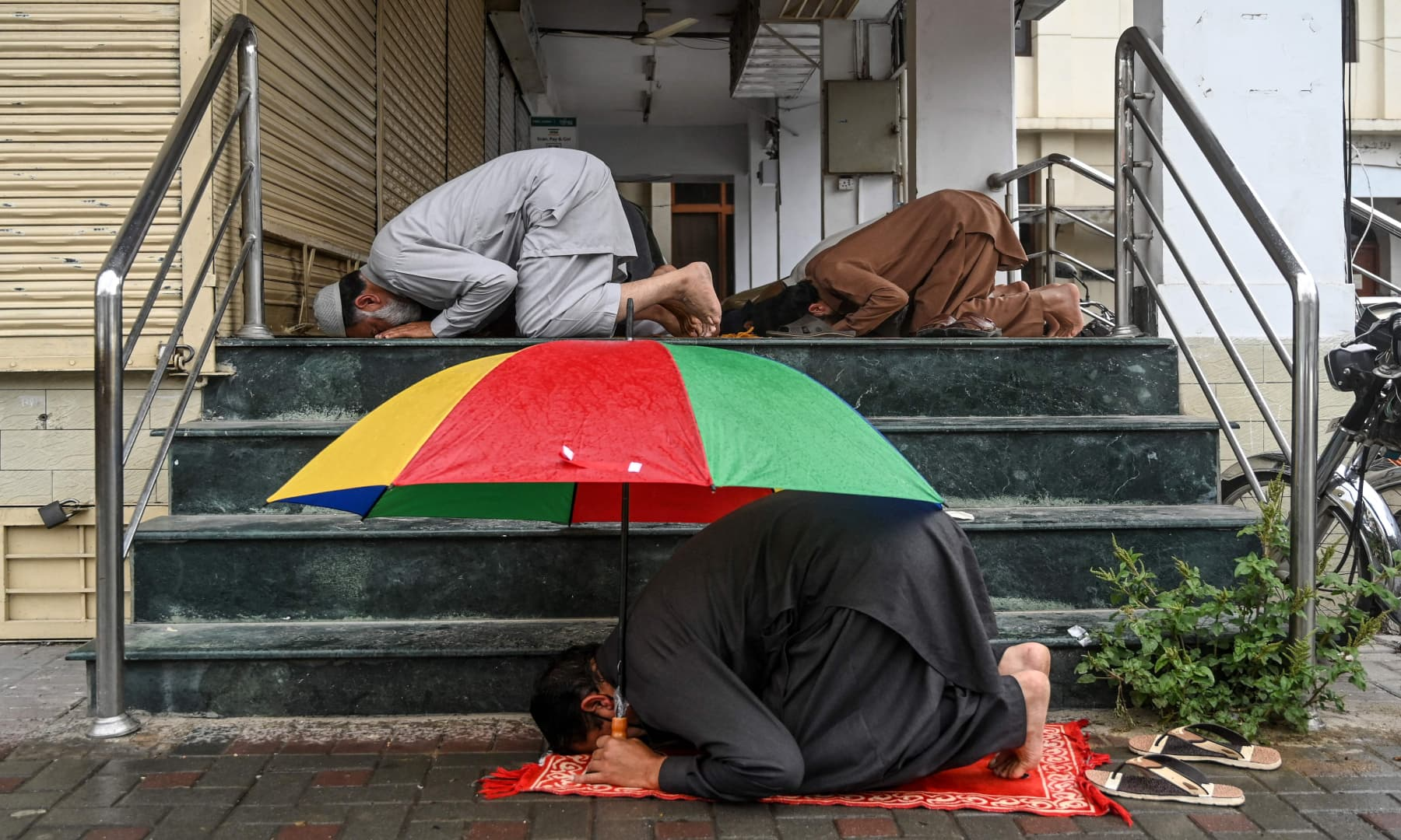 A worshipper holds an umbrella as he offers Friday prayers along with others outside a mosque in Islamabad. — AFP