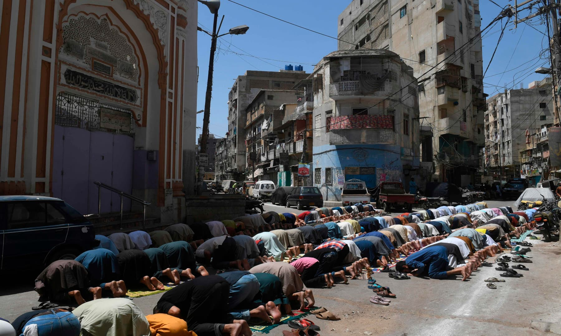 Muslim devotees offer Friday prayers outside a closed mosque in Karachi. — AFP
