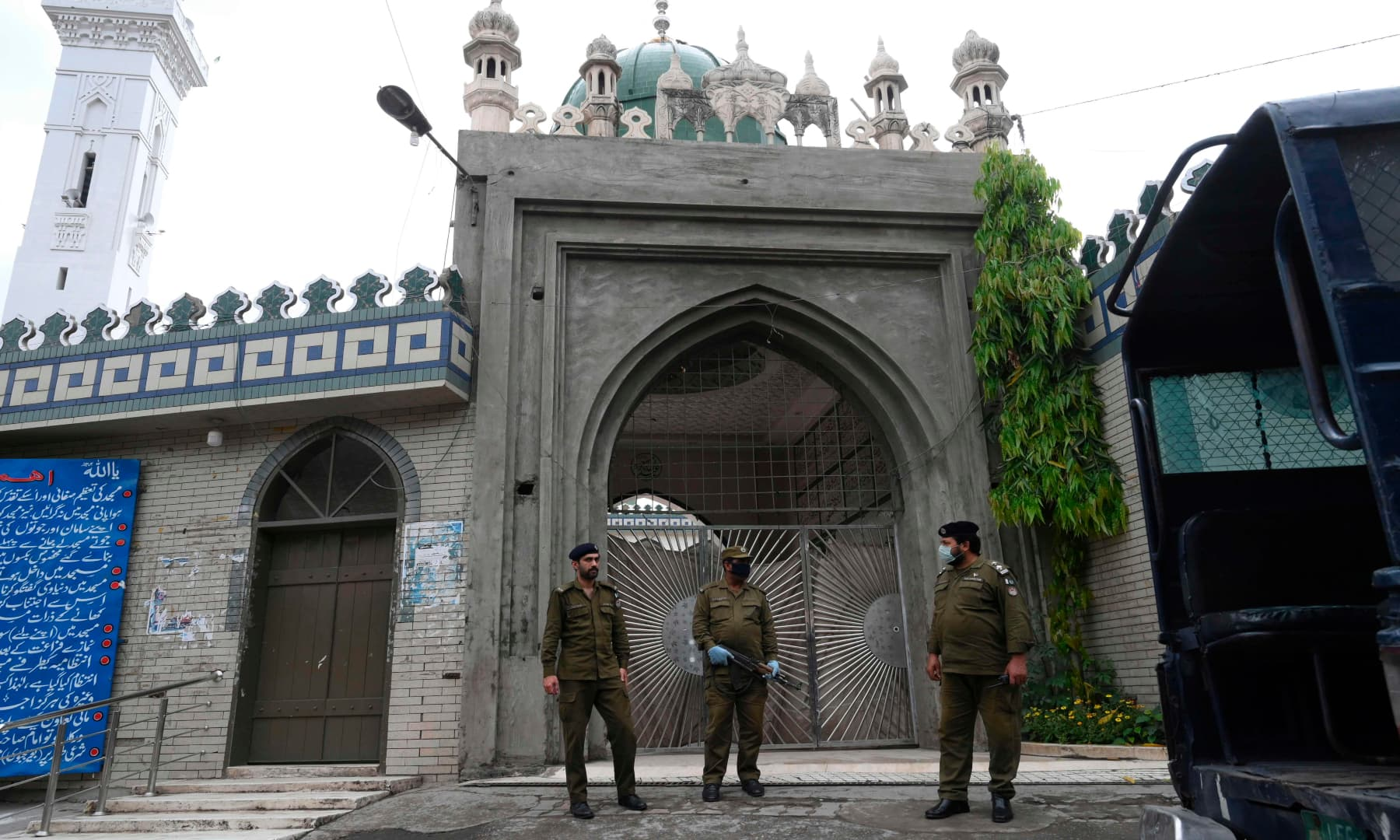 Policemen wearing facemasks stand guard outside a closed mosque in Lahore. — AFP