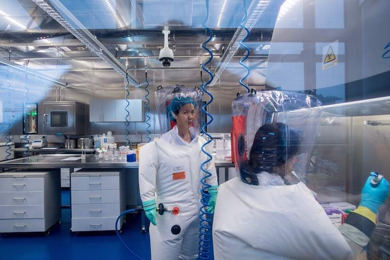 This file photo taken on February 23, 2017, shows workers inside the P4 laboratory in Wuhan, capital of China's Hubei province. The P4 epidemiological laboratory was built in collaboration with French bio-industrial firm Institut Merieux and the Chinese Academy of Sciences. The facility is among a handful of labs around the world cleared to handle Class 4 pathogens (P4) — dangerous viruses that pose a high risk of person-to-person transmission. — AFP