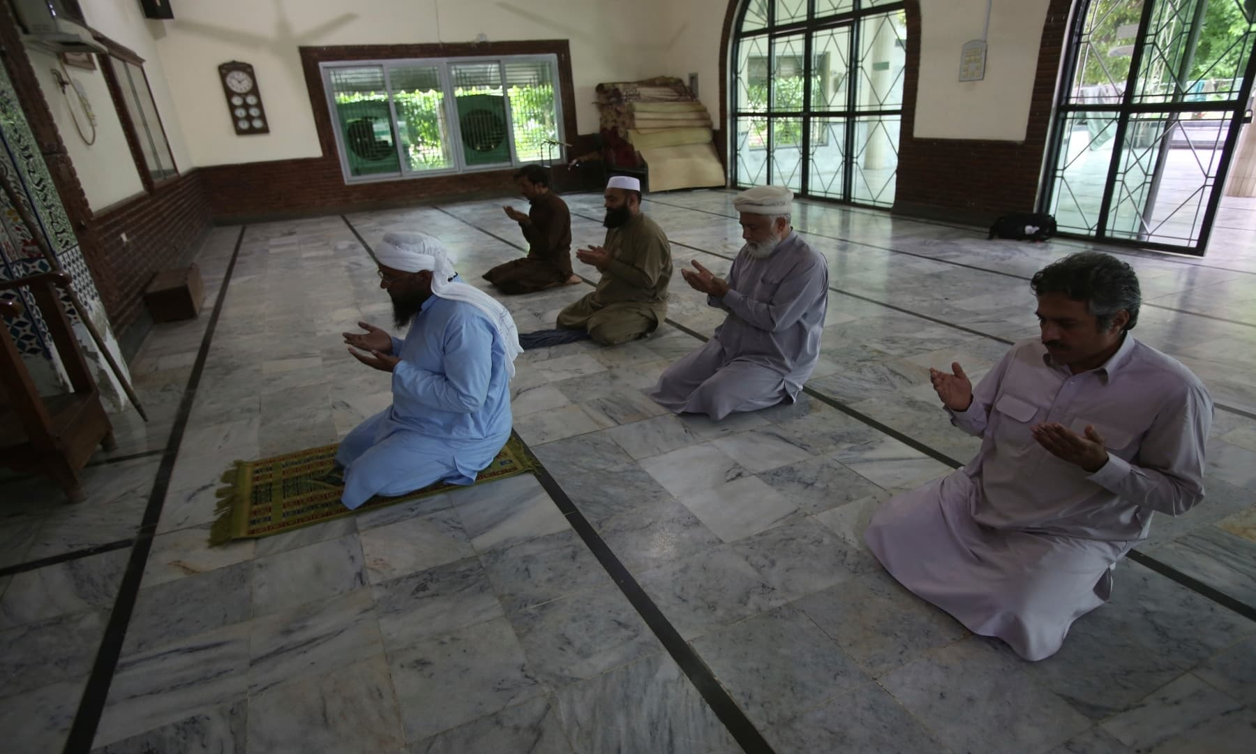 Five people attend Friday prayers at a mosque in Peshawar, maintaining distance as per the directives of the government. — AP