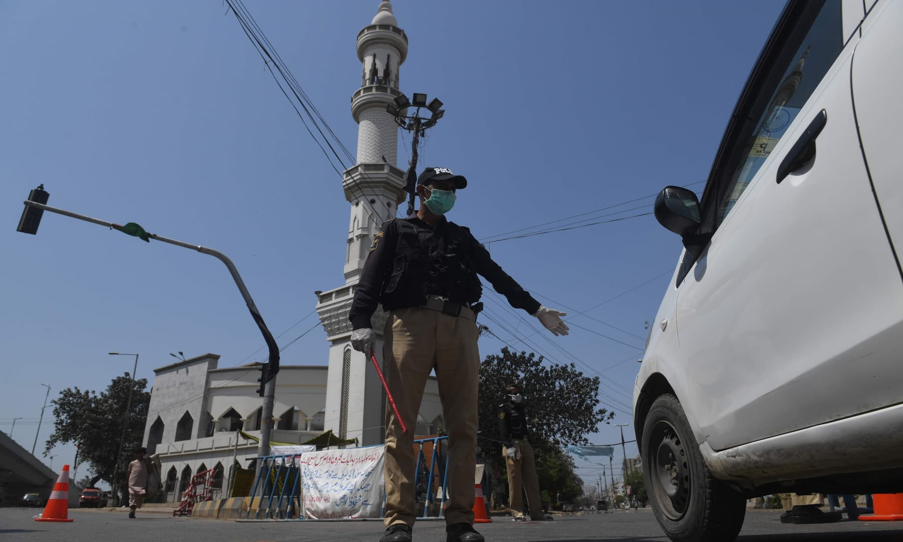 A policeman wearing a facemask stops a commuter beside a closed mosque during Friday prayers in Karachi. — AFP