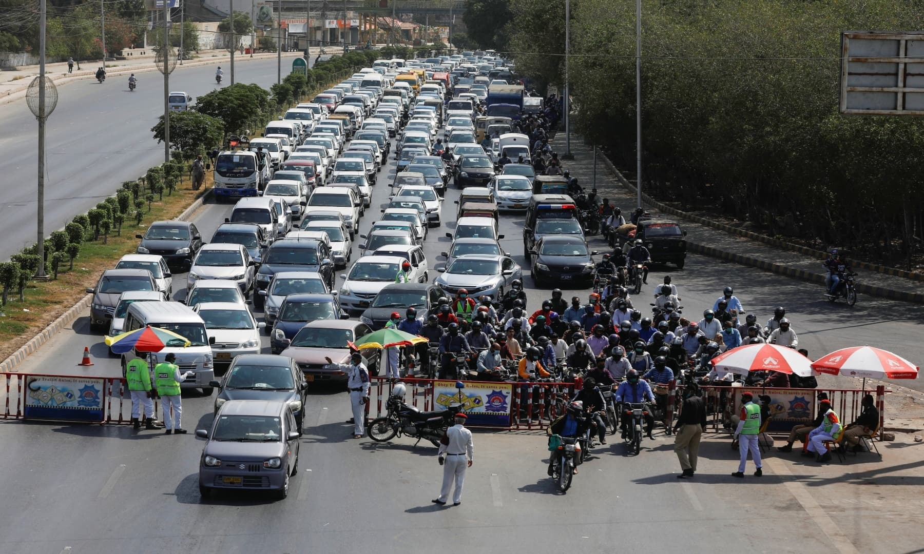 Police officers check commuters' documents to verify the purpose of movement at a blocked road in Karachi. — Reuters