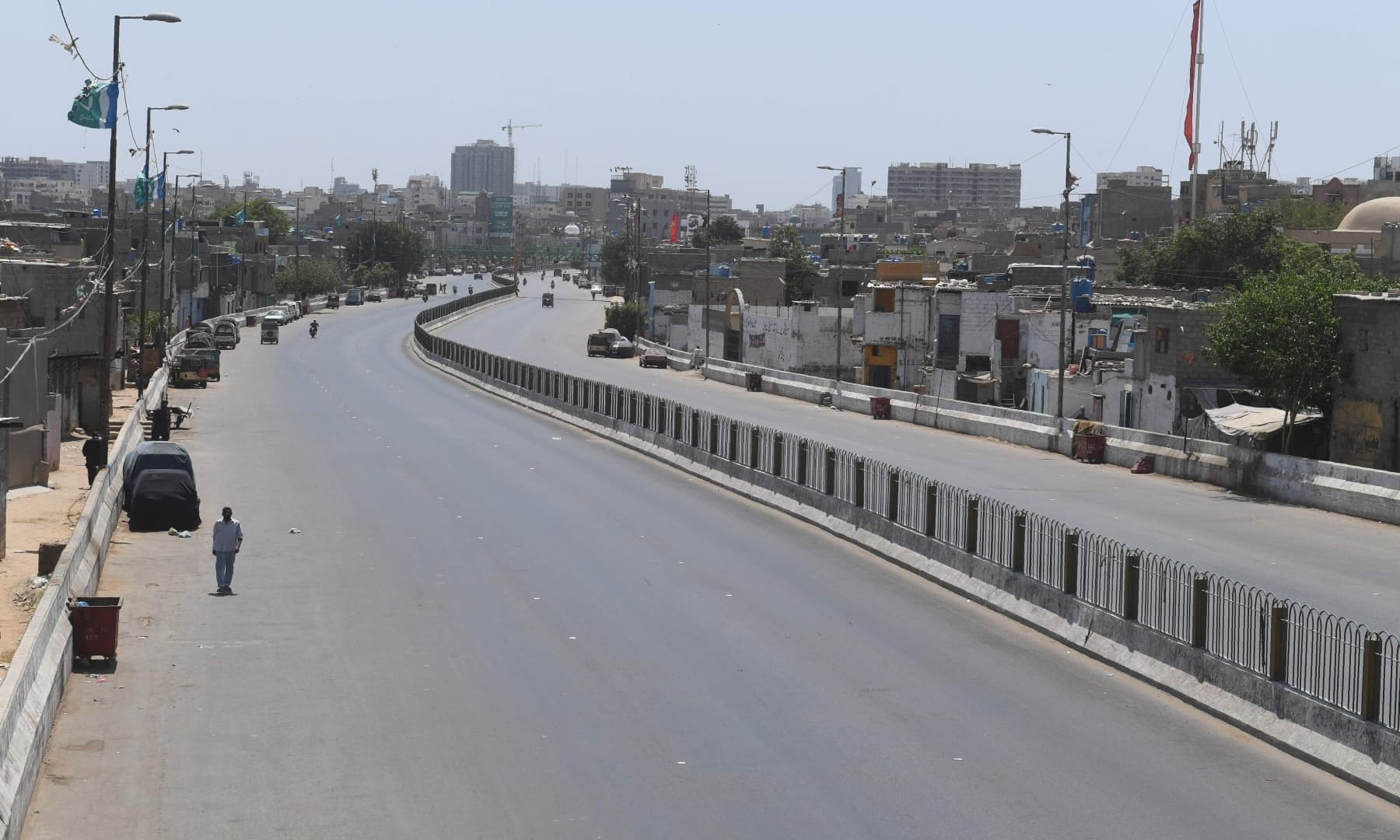 A man walks on a deserted street in Karachi. — AFP
