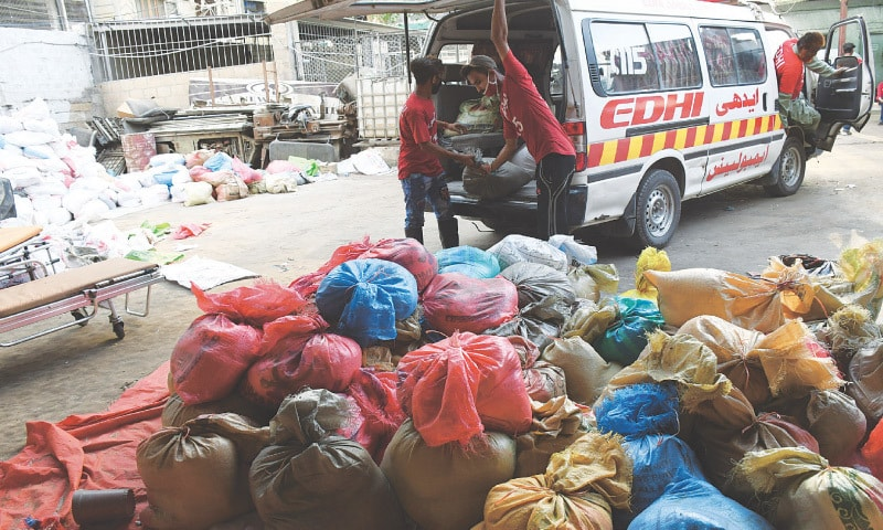 EDHI volunteers load ration bags into an ambulance for distribution on Sunday.—White Star
