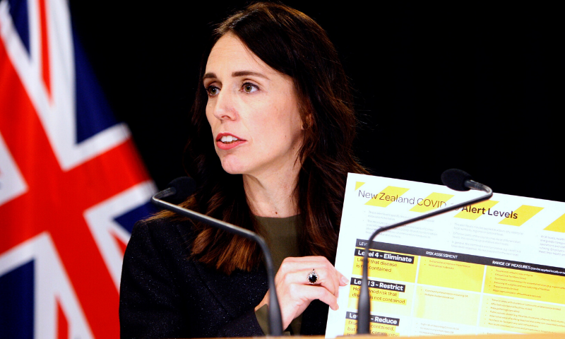 New Zealand Prime Minister Jacinda Ardern holds up a card showing a new alert system for Covid-19 in Wellington, New Zealand. — AP