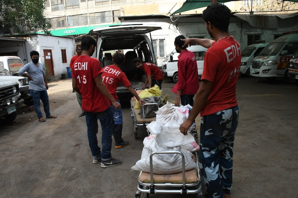 Edhi volunteers use a medical stretcher as a trolley to transport sacks of ration into a van | Faysal Mujeeb/White Star