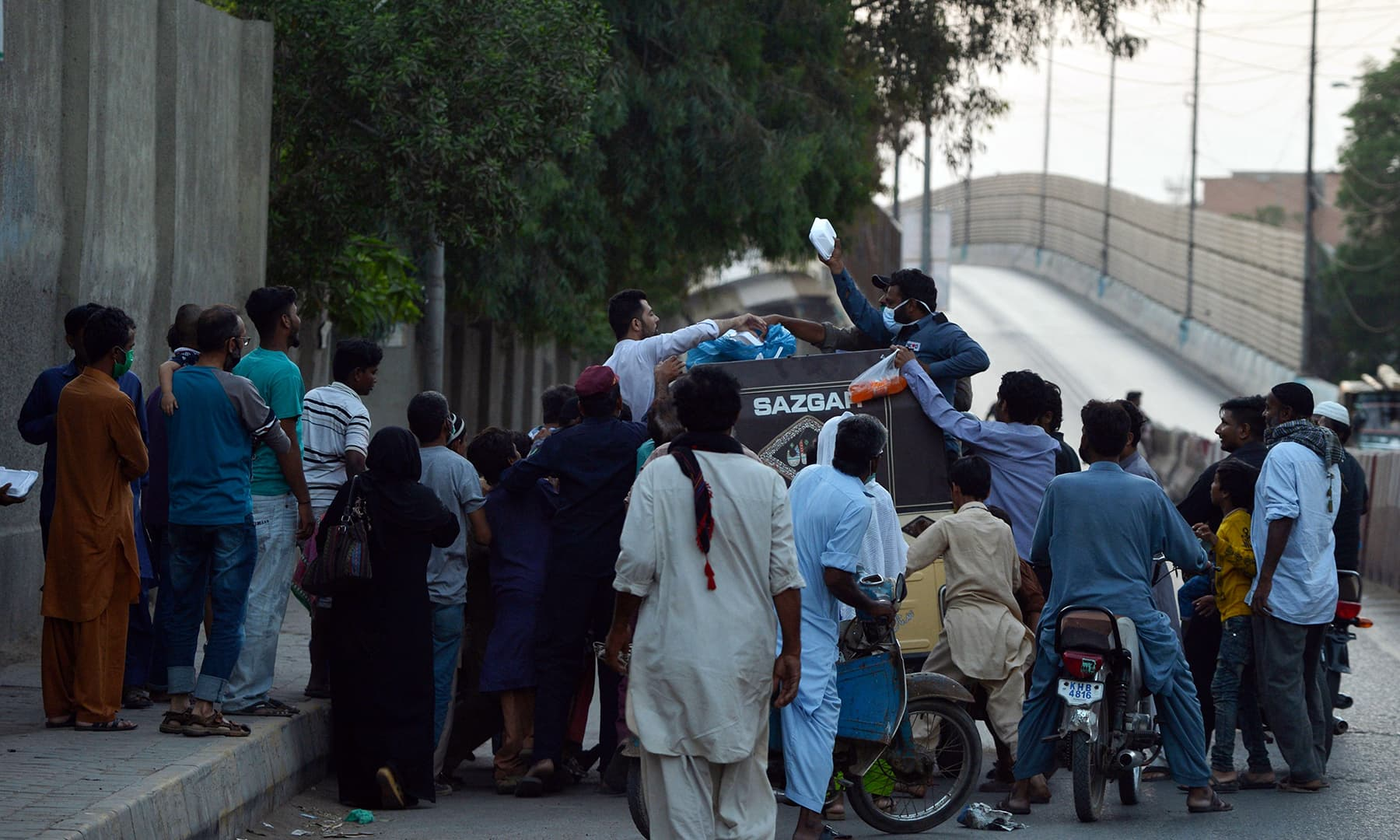 Men distribute food to people on the first day of Ramazan in Karachi. — AFP