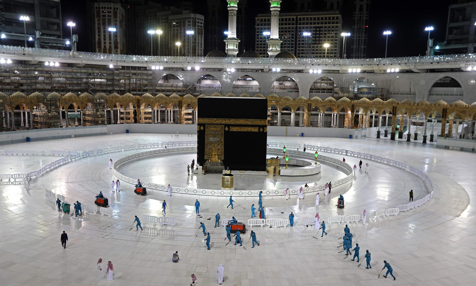 Sanitation workers disinfect the area around the Kaaba in Makkah's Grand Mosque, on the first day of Ramazan. — AFP