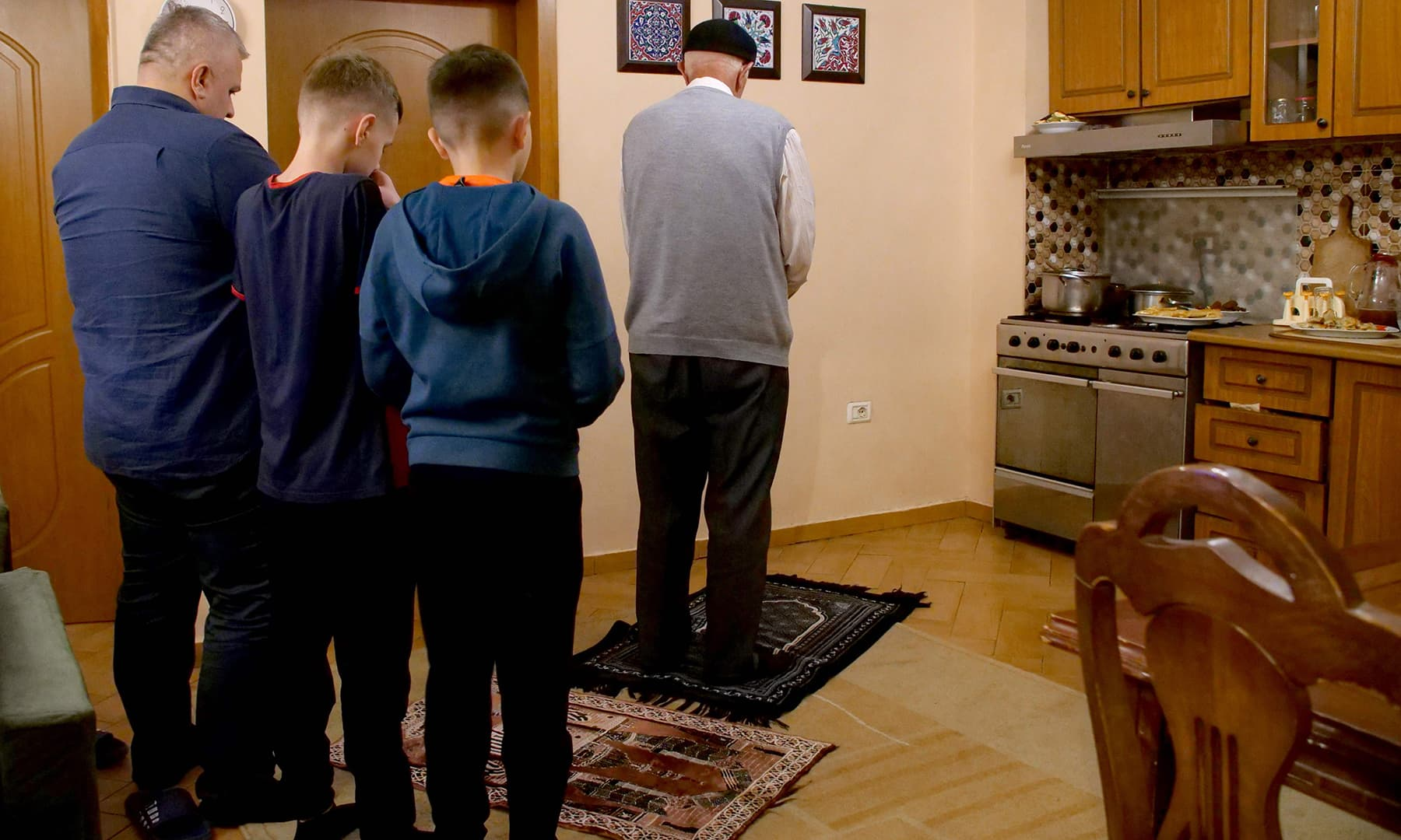 Grandfather Osman Hoxha (C), his son Agron Hoxha (L) and his grandchildren pray at their home prior the iftar during Ramazan in Tirana, Albania on April 24. — AFP