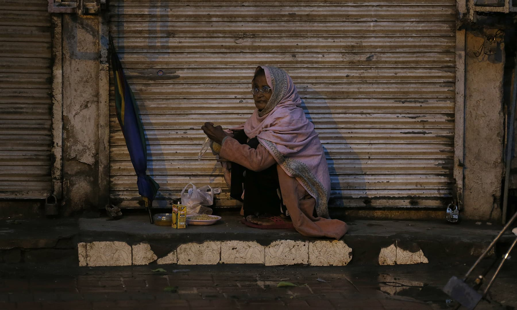 A woman breaks her fast with free food from a nearby restaurant in Rawalpindi, Saturday. — AP