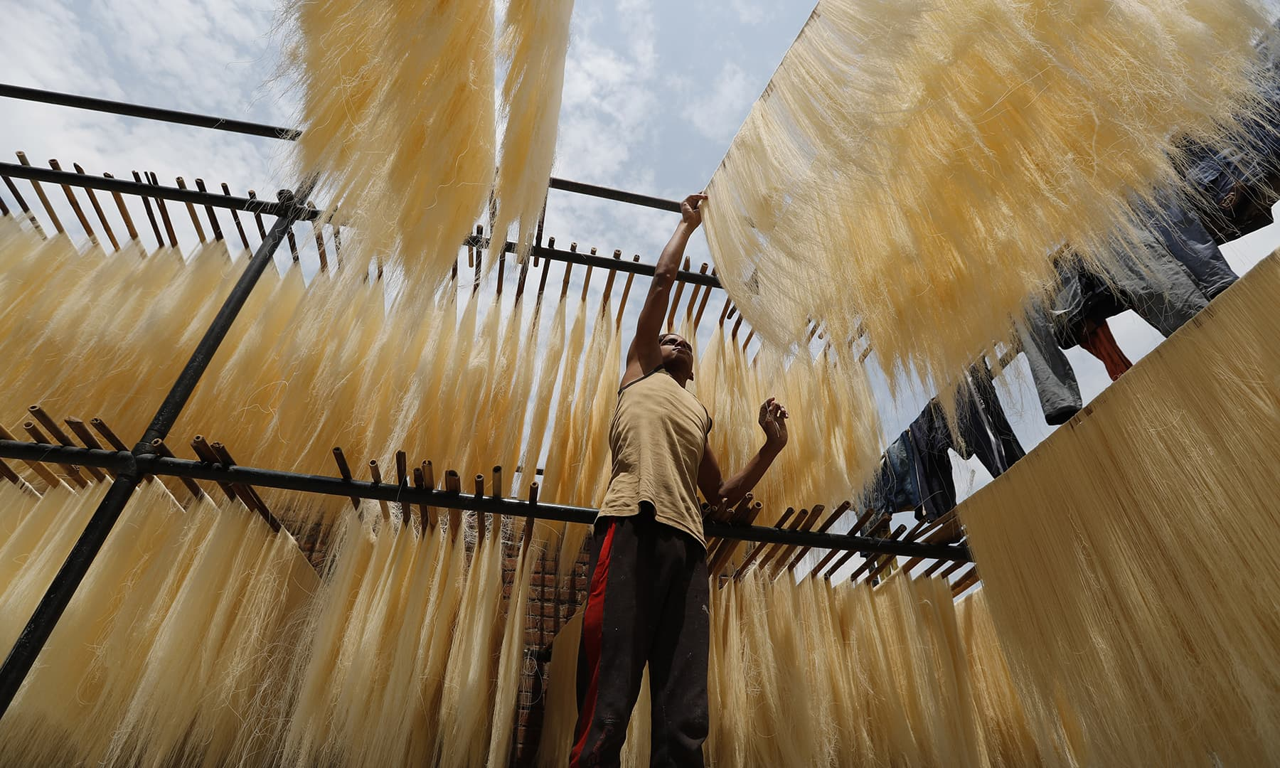 An Indian worker hangs strands of vermicelli to dry at a factory in Prayagraj, India, Saturday. — AP