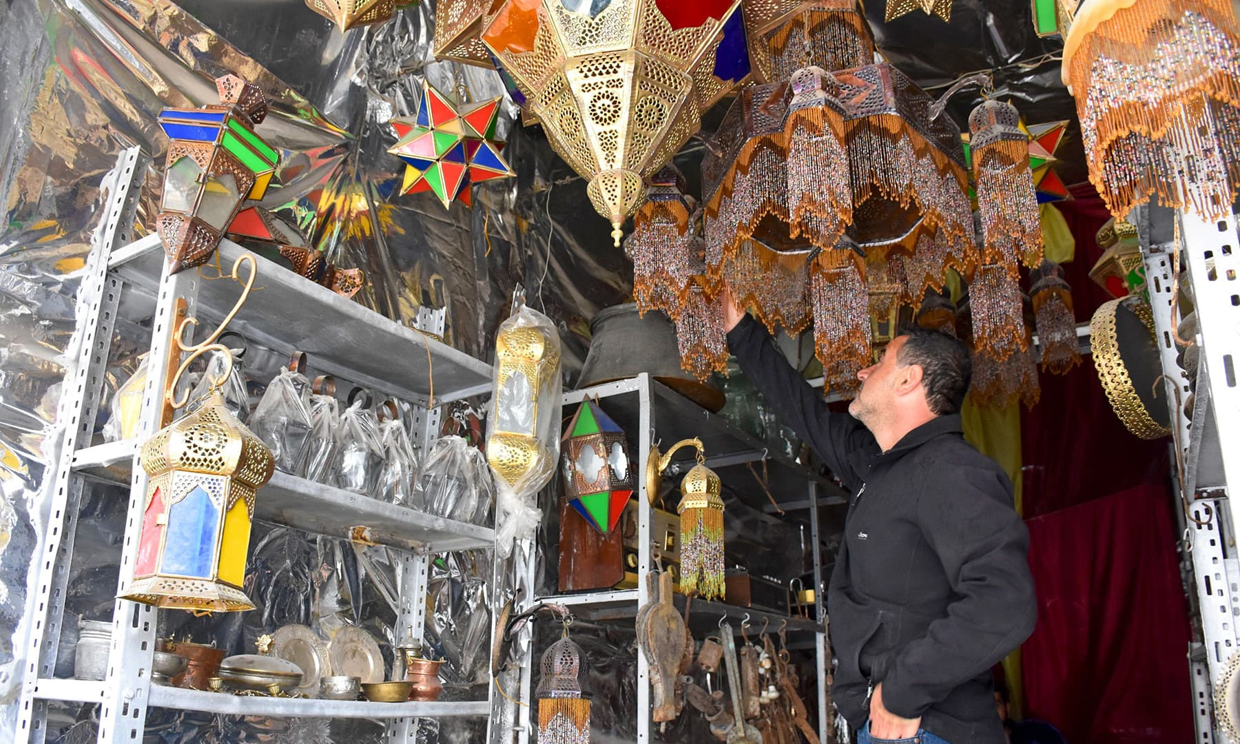 "A Syrian craftsman displays traditional ""fanous"" lanterns at his shop in the old city of Aleppo. — AFP"