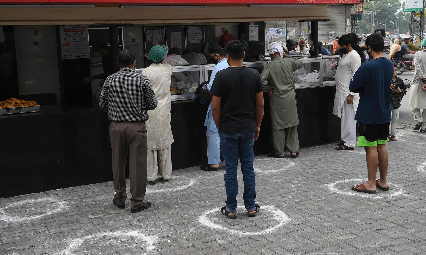 Muslim people maintaining social distance stand in line to buy food for Iftar on the first day of Ramazan in Lahore. — AFP