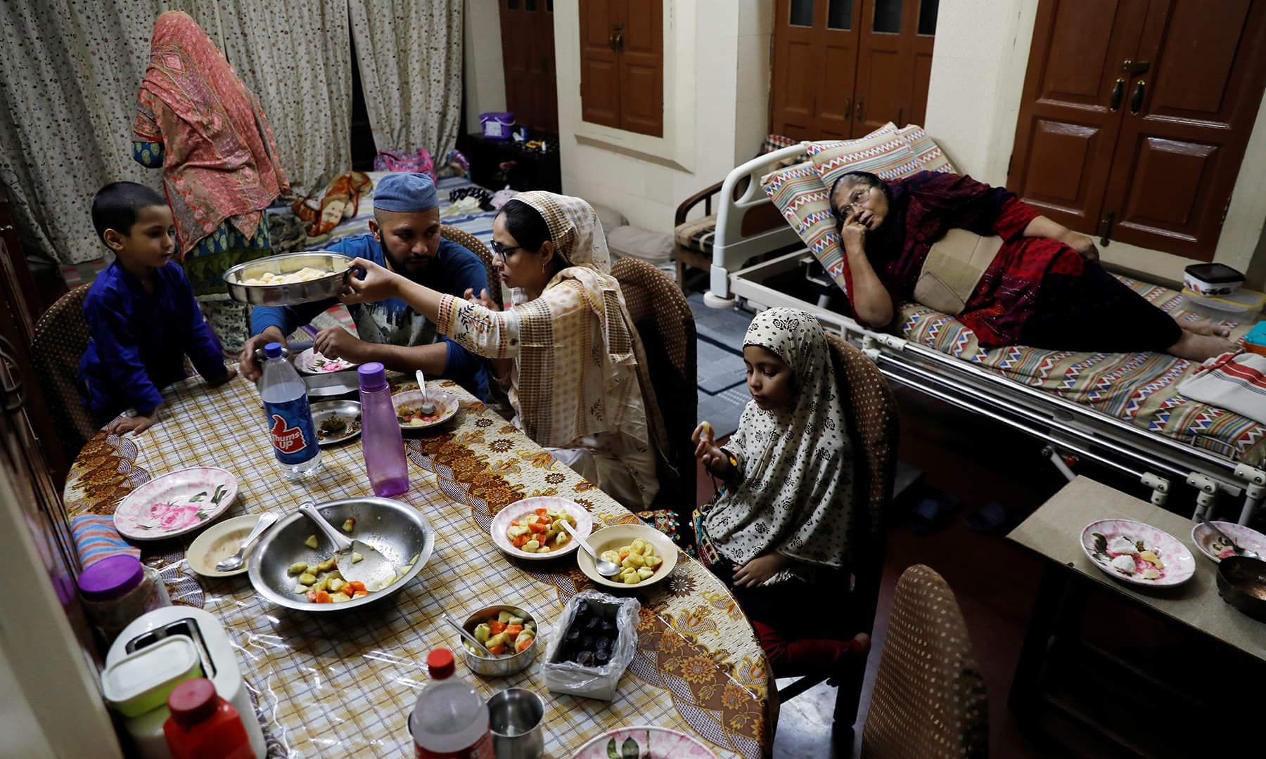 Gohar Sultan (70) looks on as her family eats an Iftar meal at their house in the old quarters of Delhi, India, April 25. — Reuters