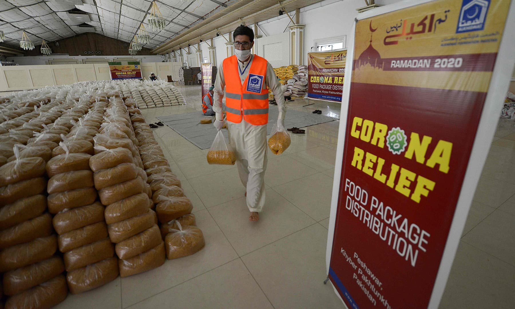 An activistof Al-Khidmat Foundationarranges food for distribution inPeshawar on April 25. — AFP