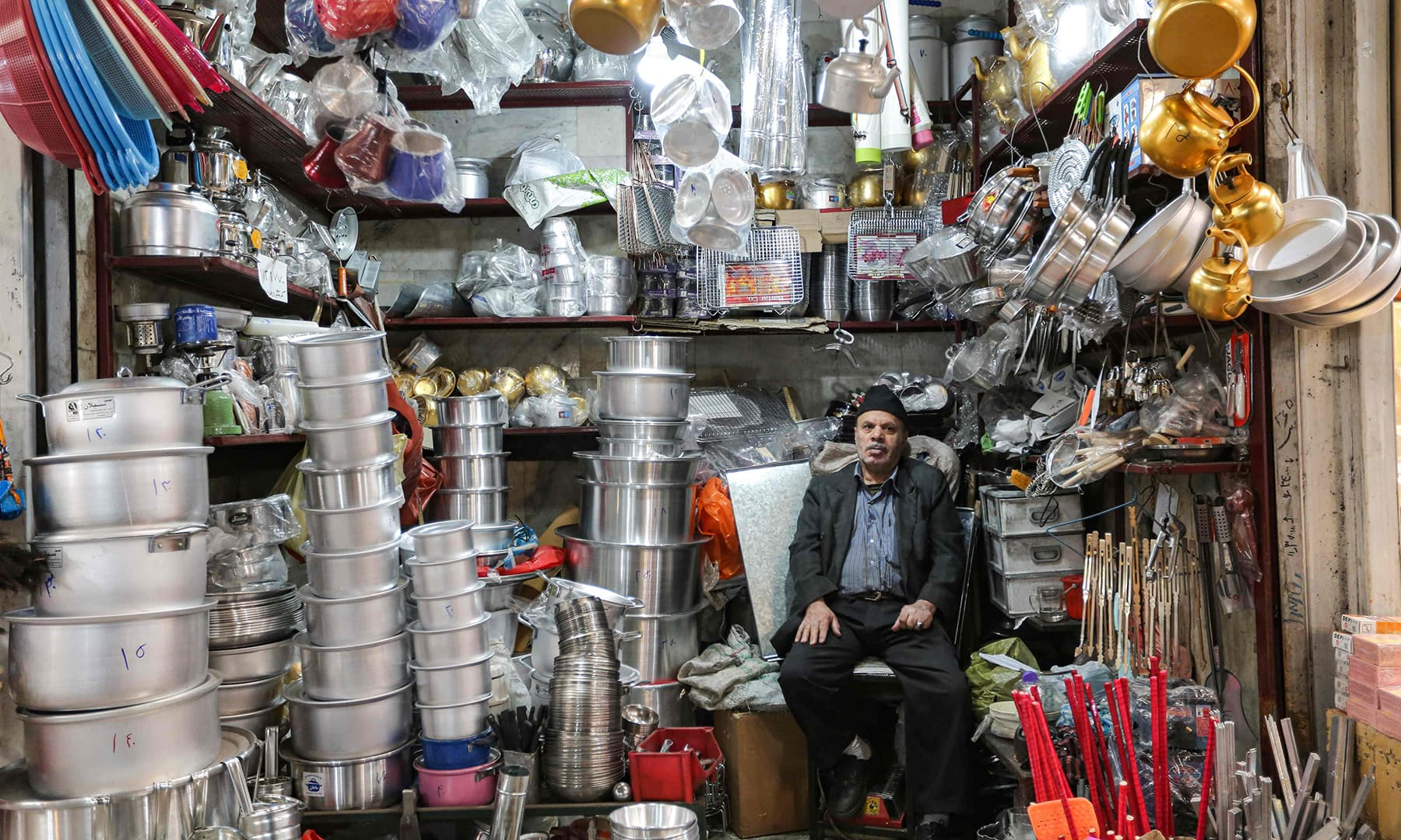 A merchant selling kitchenware sits in his shop waiting for customers in Tajrish Bazaar in Iran's capital Tehran on April 25, during Ramazan. — AFP