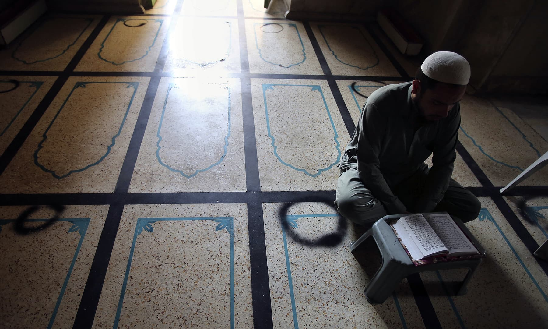 A worshipper recites the Holy Quran at a mosque during the first day of Ramazan in Peshawar. — AP