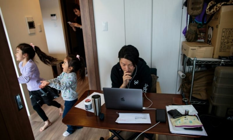 While her daughters play in the room next door, Yuki Sato, a Japanese employee of a start-up company, works at home. — AFP/File