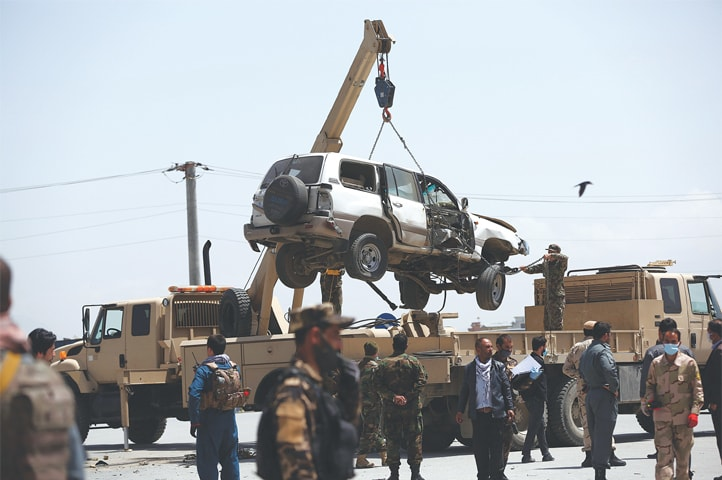 KABUL: A damaged vehicle is being removed from the site of a bomb explosion on Monday.—AP