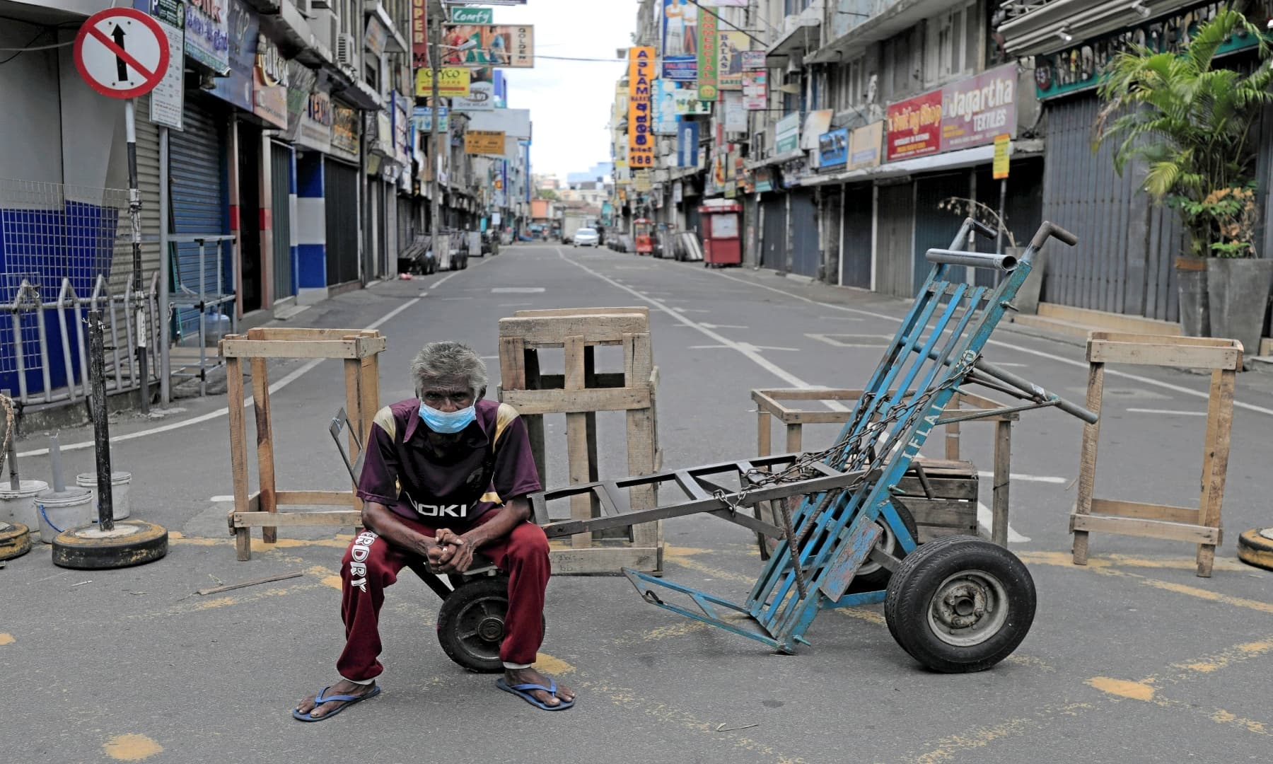 A labourer sits on a cart in a street with closed shops near the main market on Labour Day, during a curfew amid concerns about the spread of Covid-19 in Colombo, Sri Lanka. — Reuters