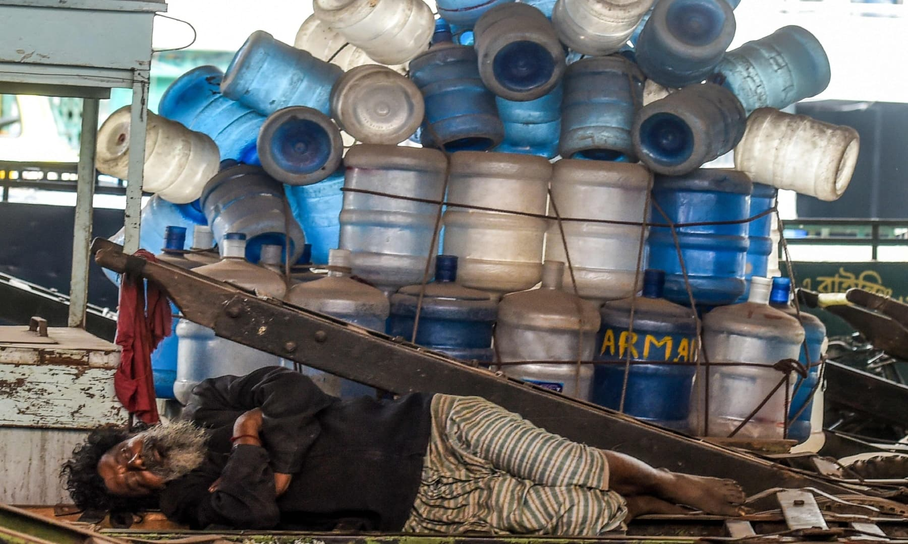 A labourer sleeps near empty water bottles on Labour Day in Dhaka, Bangladesh. — AFP