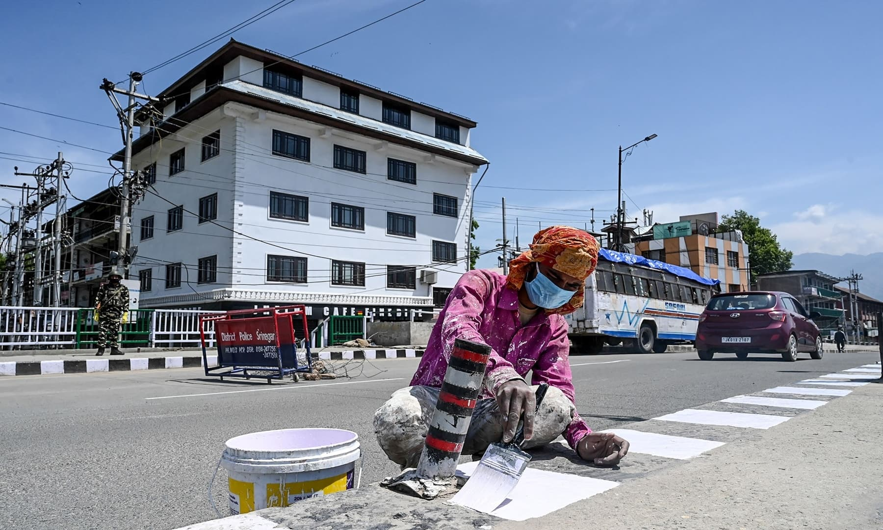 A migrant labourer paints white road markings on Labour Day in Srinagar, Indian-occupied Kashmir. — AFP