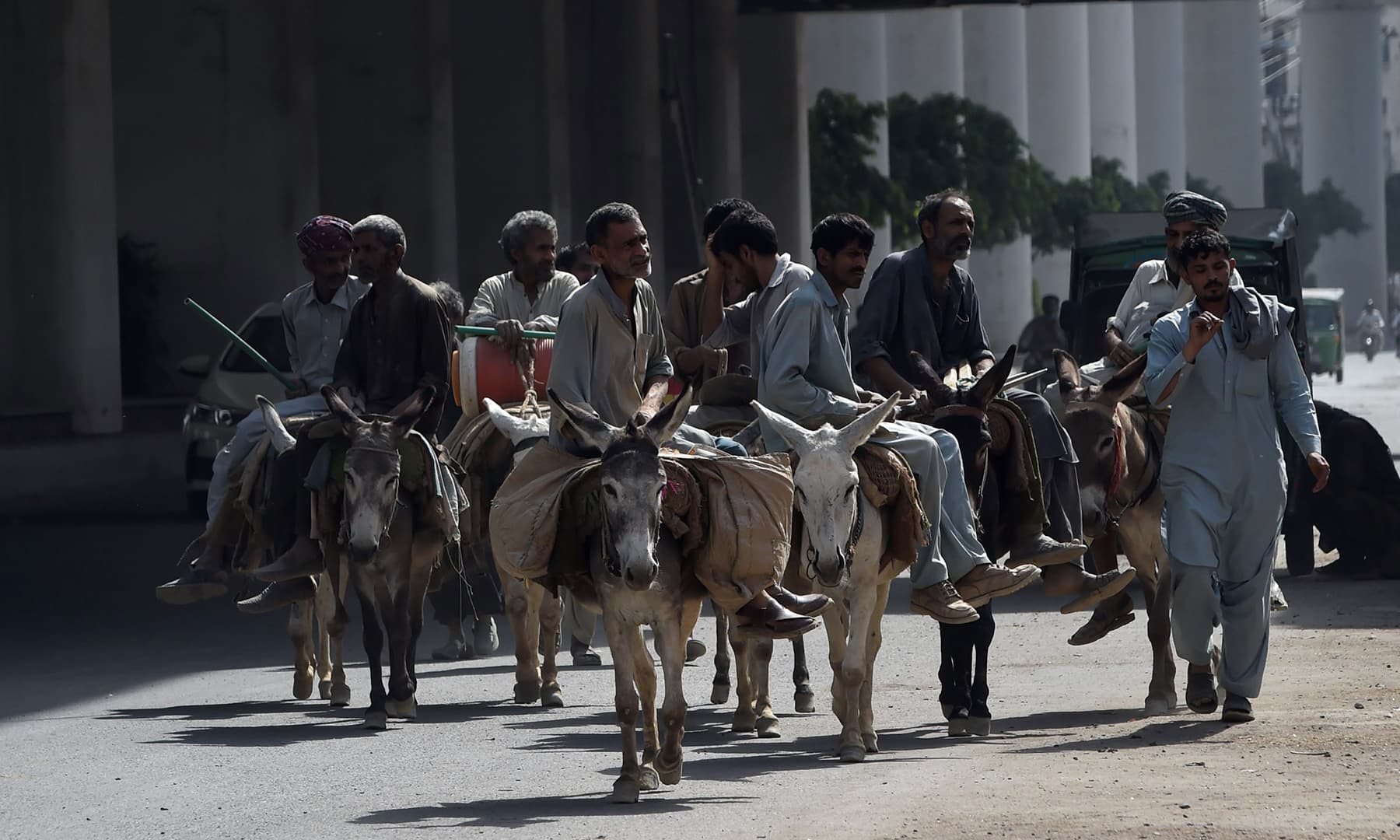 Labourers ride on their donkeys on a street during the International Labour Day in Lahore. — AFP