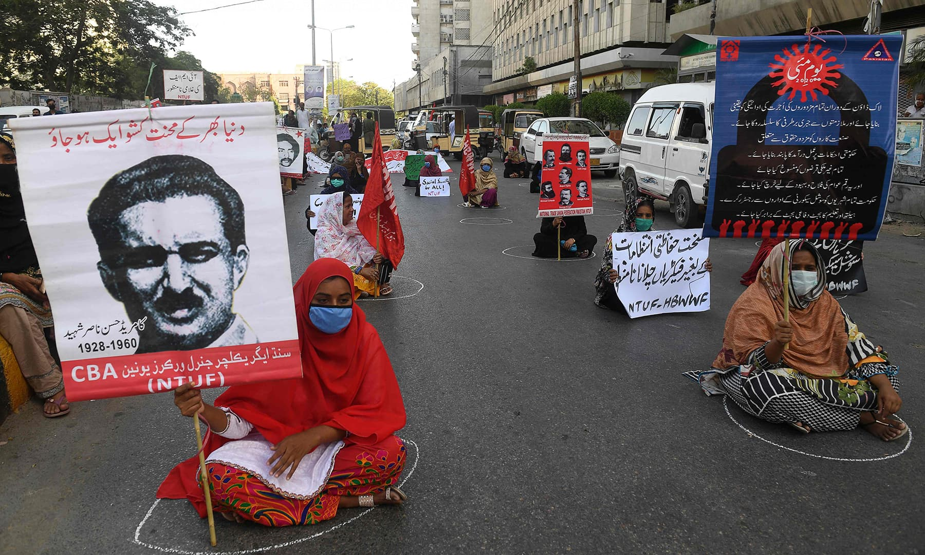 Labour union workers maintain social distancing as they carry placards during a May Day rally in Karachi on May 1. — AFP