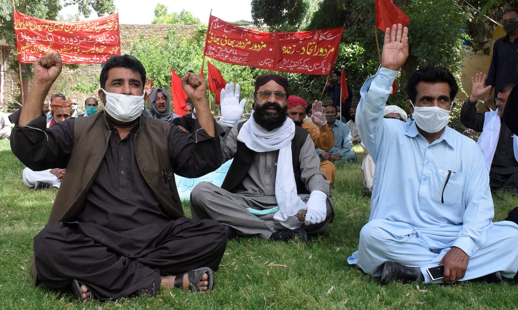 Labour union workers wearing facemasks chant slogans during a May Day rally in Quetta. — AFP