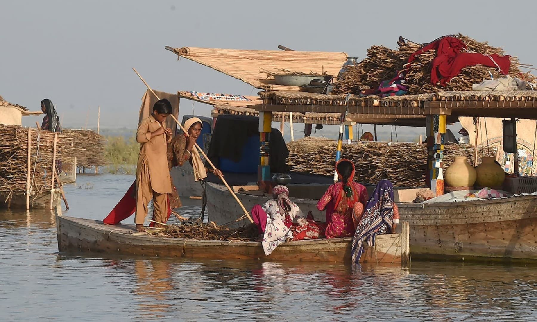 کچھ عورتیں برتن مانجھتی تھیں، کچھ کشتیوں پر کپڑے اور رلیاں دھوپ میں سوکھنے کے لیے پڑی تھیں—مصطفیٰ میرانی