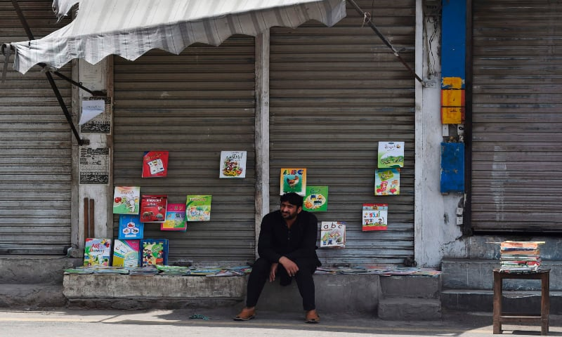 A man waits for customers as he sells books during a government-imposed nationwide lockdown as a preventive measure against the Covid-19 coronavirus, in Lahore on May 3. — AFP