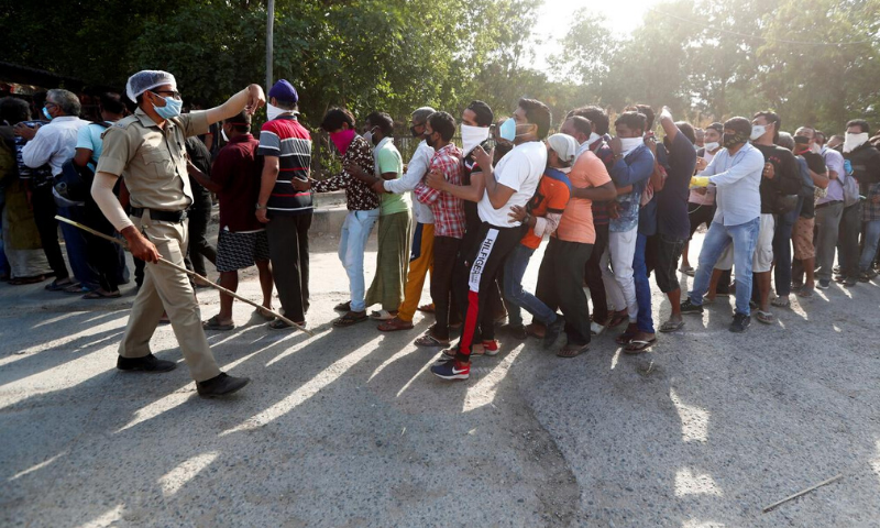 A police officer tries to control the crowds outside a wine store during an extended nationwide lockdown to slow down the spread of the coronavirus, in New Delhi, India on Monday. — Reuters