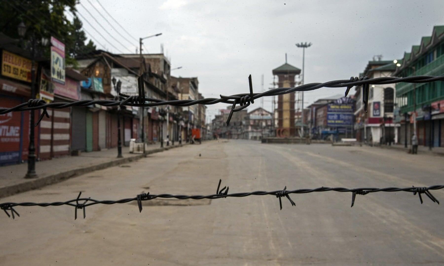 A deserted street is seen through barbwire set up as a blockade during curfew in Srinagar on August 6, 2019. — AP/Dar Yasin)