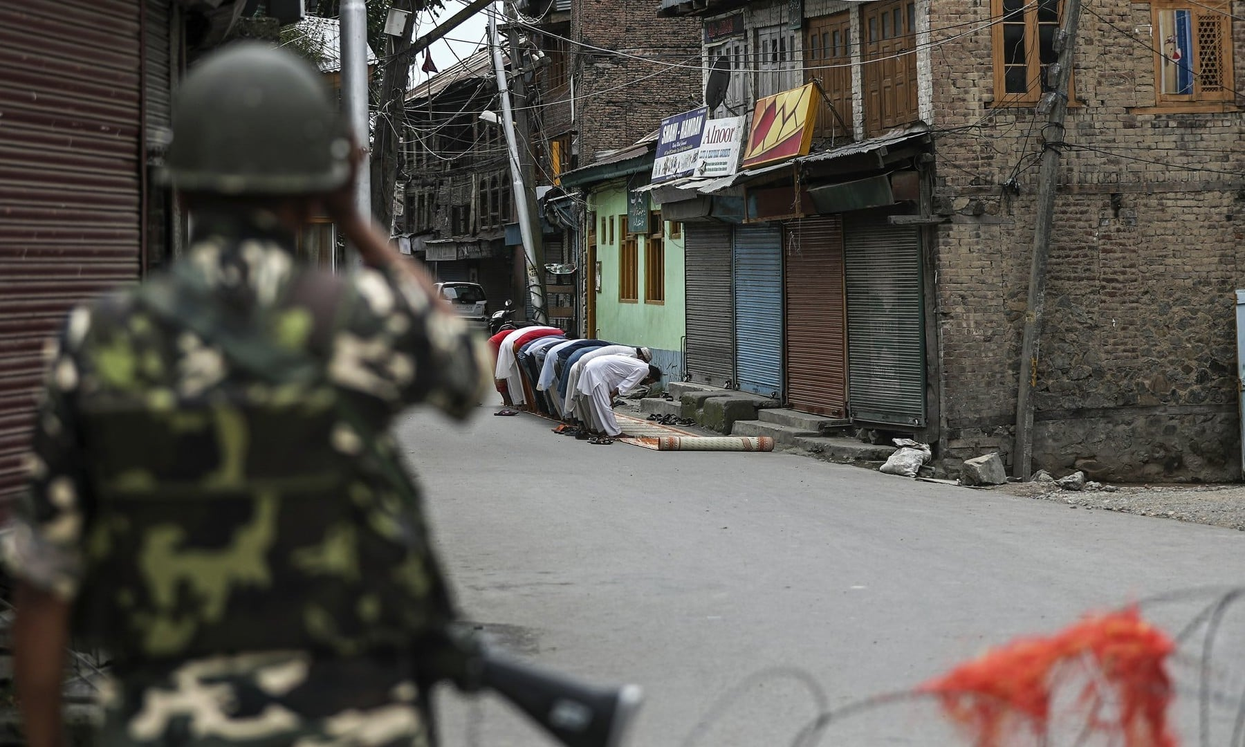 An Indian paramilitary soldier stands guard as Kashmiri Muslims offer Friday prayers on a street outside a local mosque in Srinagar on August 16, 2019. — AP/Mukhtar Khan