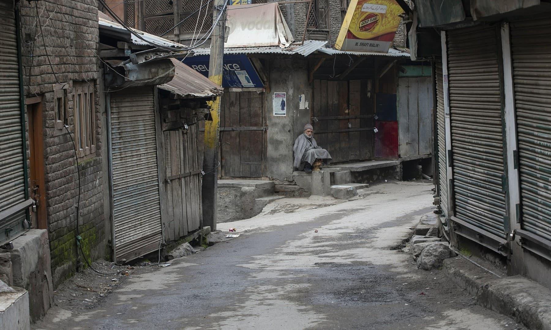 An elderly Kashmiri man sits outside a closed market during a strike in Srinagar on February 17, 2019.  — AP/Dar Yasin