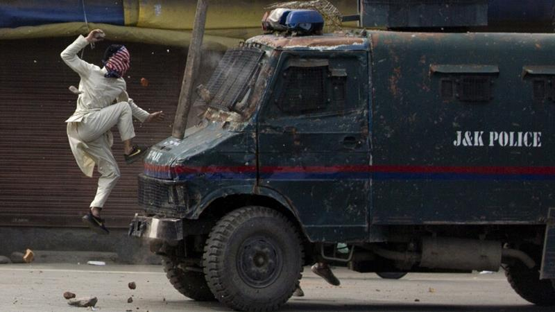 A masked Kashmiri protester jumps on the bonnet of an armoured vehicle of Indian police as he throws stones at it during a protest in Srinagar. — AP/Dar Yasin