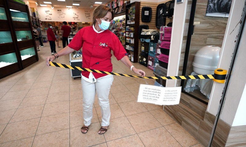 Store manager Natalie Hijazi temporarily closes off the entrance to a Pet Fair store inside The Woodlands Mall to help meet the current occupancy limits in place on Tuesday. — AP