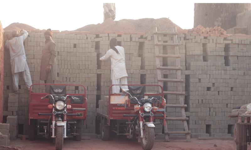 Labourers stacking bricks in a zig-zag pattern.