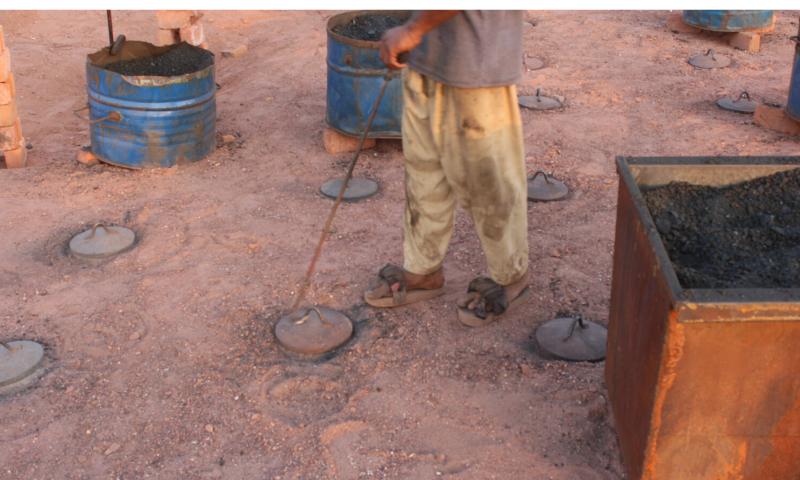 A labourer feeds coal in the brick kiln through feeding hole.