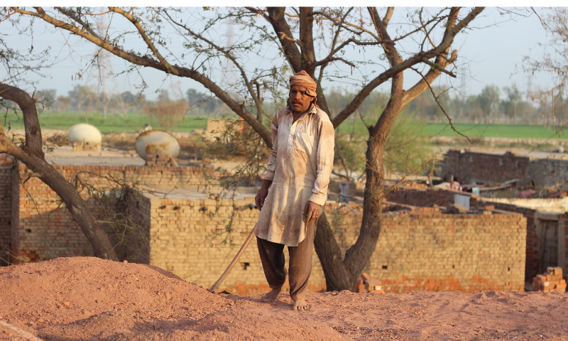 As the stacking of bricks is being done, a labourer covers it with soil.
