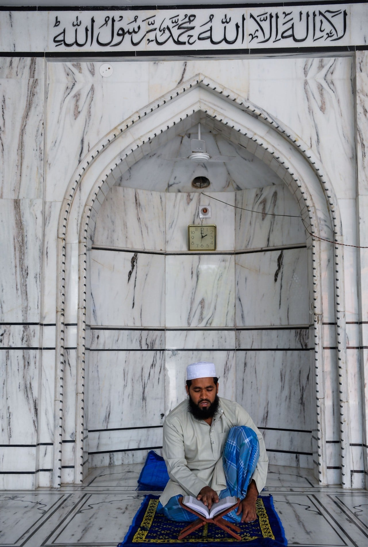 n this picture taken on May 4, a Muslim devotee reads a copy of the Quran at a mosque in Delhi.  — AFP