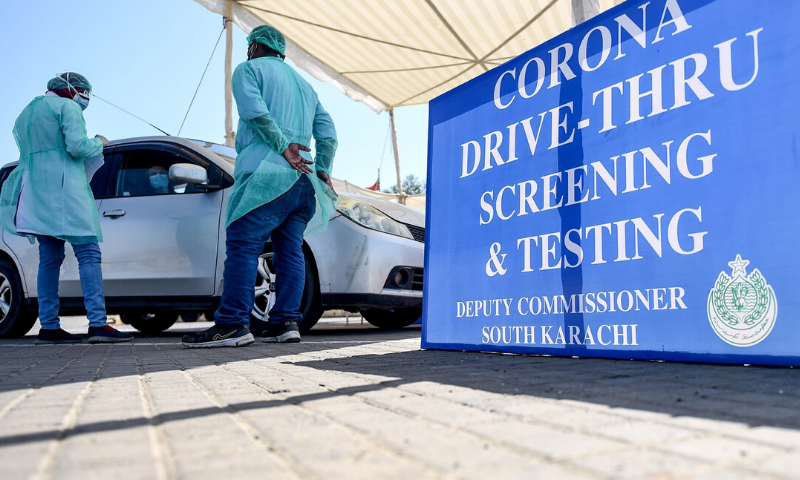 Medical staff members take information from a resident sitting in a car for a coronavirus test at a drive-through testing facility in Karachi. — AFP