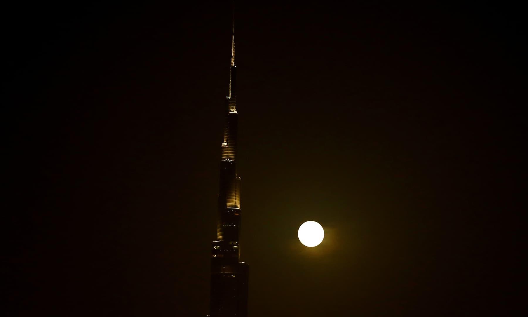 The full moon rises next to Burj Khalifa, the world's tallest building, in Dubai, United Arab Emirates. — Reuters