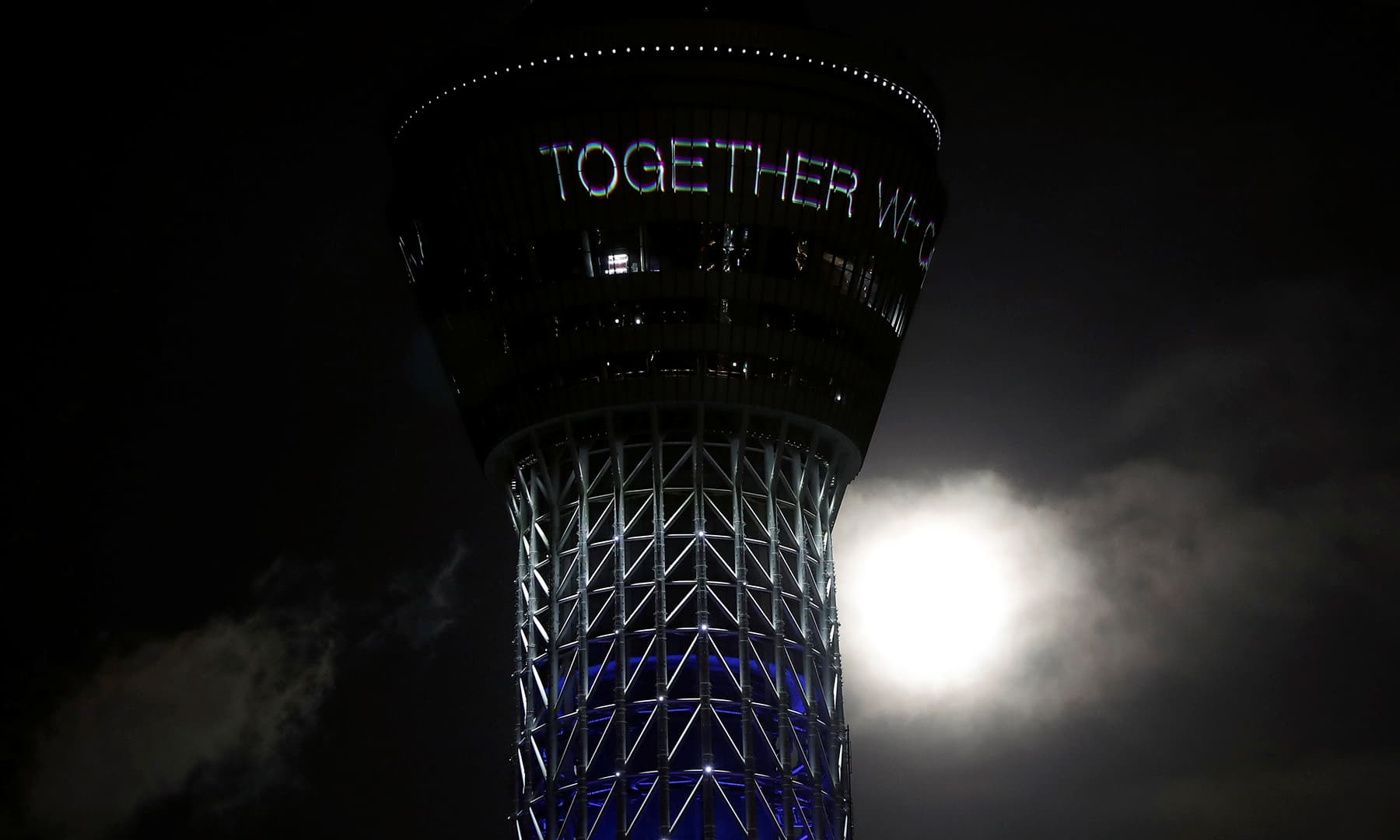 """The full moon rises next to Tokyo Skytree which is displaying a message reading """"Together we can all win"""" and illuminated in blue to honour first responders and essential workers as the outbreak of the coronavirus continues, in Tokyo, Japan. — Reuters"""